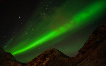 grain and noise bright glow green northern aurora lights in clear sky at night in Lofoten Islands, Norway