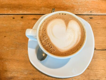 heart shape of latte art on hot coffee cup on wooden table in cafe Stock Photo