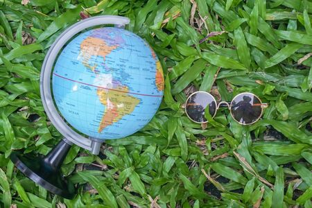 holidays concept with round vintage sunglasses and globe for exploring and travelling on green yard