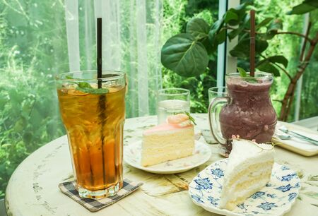 peach tea and blueberry smoothie with tasty butter cake for teatime in cafe