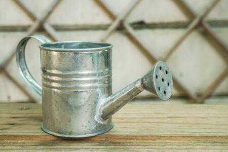 steel can flower pot in home garden for watering plants
