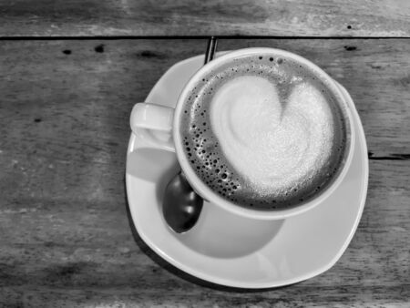 black and white color heart shape of latte art on hot coffee cup on wooden table in cafe Stock Photo