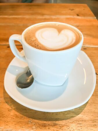 close up heart shape of latte art on hot coffee cup on wooden table in cafe