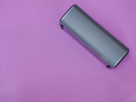 portable speaker on pink pastel background for music listening