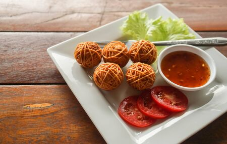 Thai traditional fried pork ball with noodles on white square plate in traditional restaurant