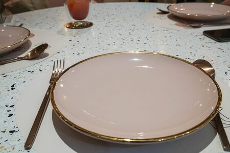 close up glowing pink gold round plate with spoon and fork on dining table in luxury restaurant 写真素材