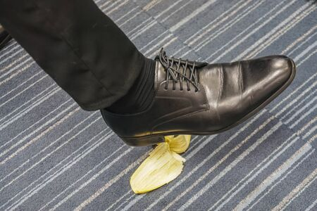 close up man with black leather shoes slips by banana peel
