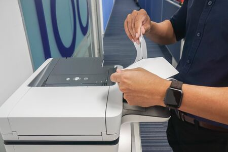 close up businessman tearing the confidential documents from office printer