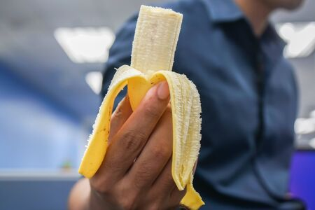close up fresh banana peel in man hand for eat