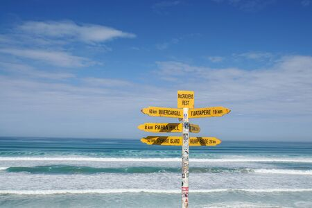 New Zealand - November 28 2018: yellow sign post for direction at Tasman Sea in sunny day