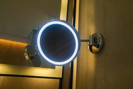 close up glowing round mirror in hotel bathroom for women make up