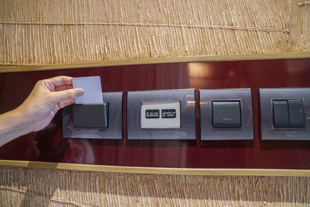 close up people put room key card in hotel for electricity