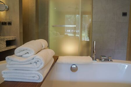 close up white soft cotton towels on white bathtub in luxury bathroom