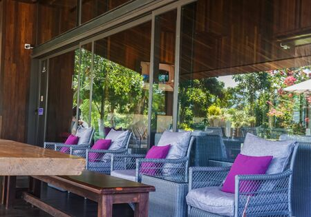 wicker chair with purple pillows for seating at house terrace