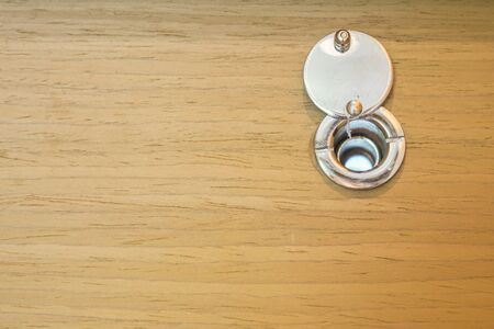 close up peephole on the hotel wooden door for looking and security before opening