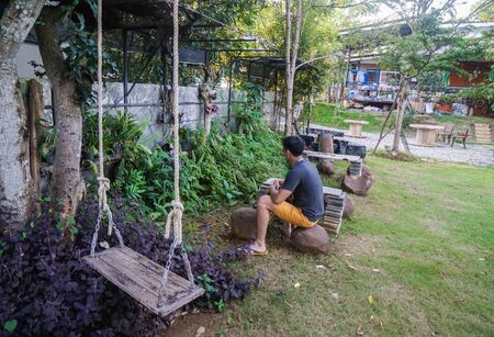 man sit on outdoor seat for gardening work in free time