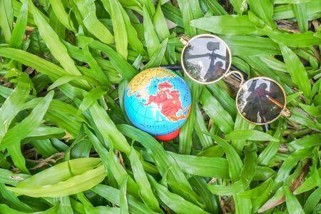 travel around the world and holiday concept - top view of round vintage sunglasses and globe on green yard in summer Stock Photo