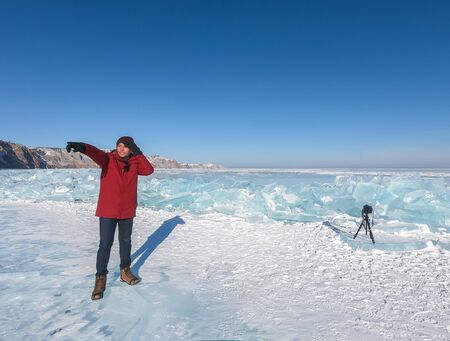 male tourist in winter coat stands on frozen Baikal lake with ice crystals Editorial