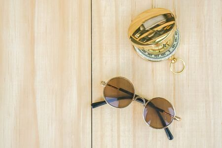 top view of round sunglasses with golden compass as travel concept Archivio Fotografico - 138031745