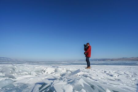 man wearing knitted hat and winter coat take photographs of frozen Baikal Lake with camera tripod