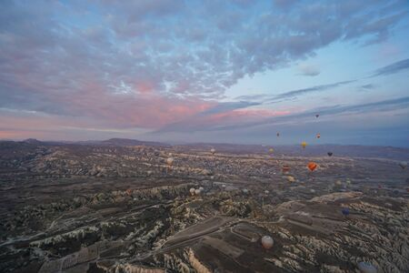 Goreme  Turkey - December 6 2019: noise and grain of mountain hill landscape in Cappadocia with hot air balloon in romantic sunrise moment