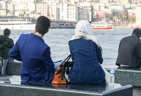 young couple sit on the bench at pier in Bosphorus in Turkey Stock Photo