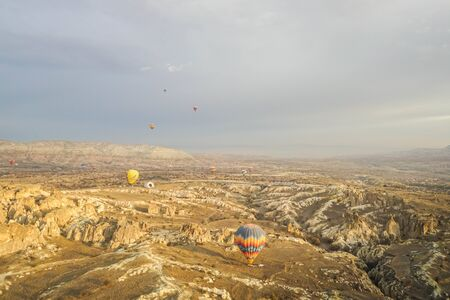 Goreme  Turkey - December 6 2019: noise and grain of mountain hill top view landscape in Cappadocia with hot air balloon in romantic sunrise moment