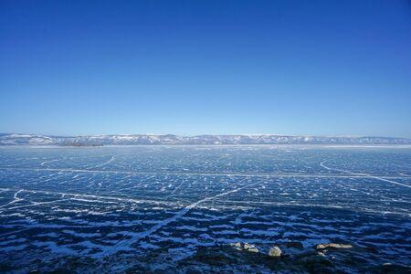deep blue frozen Baikal lake with far mountain range Stock Photo