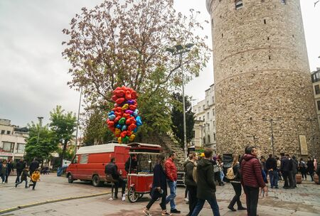Istanbul  Turkey - December 8 2019: people travel at Galata Tower with floating heart shape balloon in Taksim Square in weekends