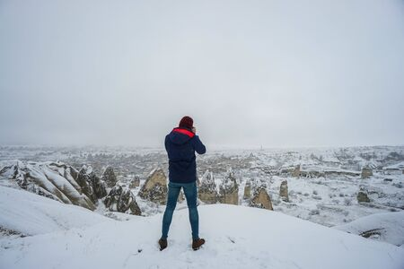 camera man with winter coat takes landscape photographs in Cappadocia winter