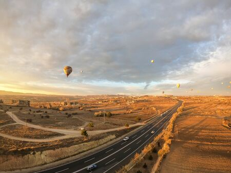 Cappadocia  Turkey - December 5 2019: long concrete road with bright morning sunlight and floating hot air balloon