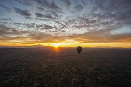 Goreme  Turkey - December 6 2019: noise and grain of mountain hill top view landscape in Cappadocia with hot air balloon in sunrise sky in the morning Editorial