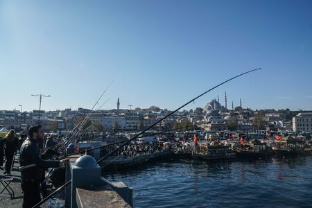 Istanbul . Turkey - December 10 2019: people are fishing on the Galata Bridge at the Black Sea with New Mosque in the morning Editorial