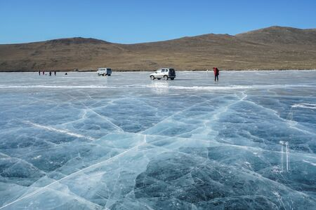 Olkhon Island  Russia - February 14 2019: Crack thick frozen Baikal lake with tourists and vintage van