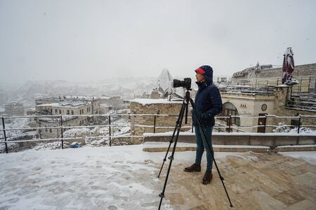 man with camera on tripod at roof top hotel for photographs of snow landscape