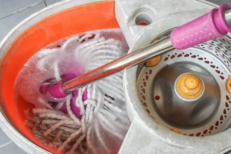 close up clean dirty mop in water in plastic bucket