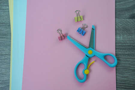 blue scissors with paper clips and colorful papers for craft work