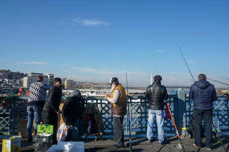 Istanbul / Turkey - December 09 2019: people make a living by fishing at Galata Bridge in winter sunny day Editorial