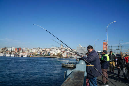 Istanbul / Turkey - December 09 2019: men make a living by fishing at Galata Bridge in winter sunny day Editorial