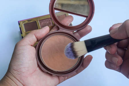 selective focus on woman hand hold bronzer for make up in the morning
