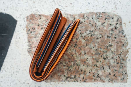 flat lay of brown men leather wallet with cash and credit card for shopping