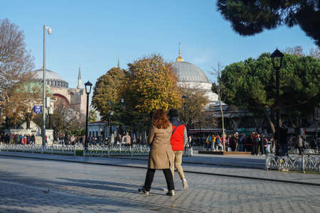 Istanbul / Turkey - December 10 2019: young couple walk at Sultanahmet Square in winter sunny day Editorial