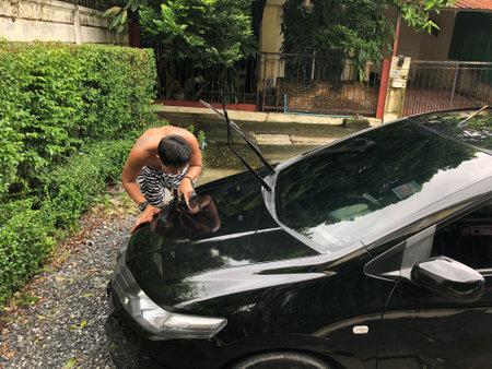Bangkok / Thailand - October 3 2020: Asian man without shirt clean his black own car 新聞圖片