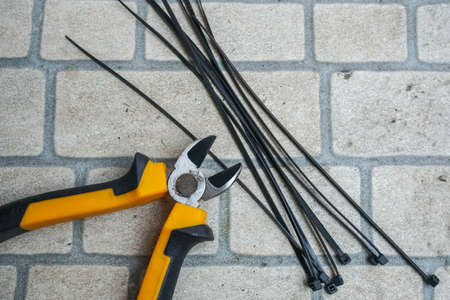 flat lay of yellow pliers with black cable ties Stock Photo