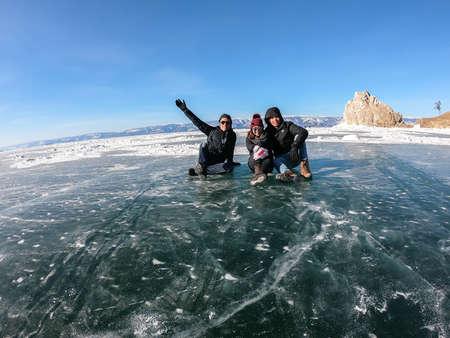 Baikal lake Irkutsk - February 14 2019: man and woman Thai people sit on frozen lake in Russia in winter Stock Photo
