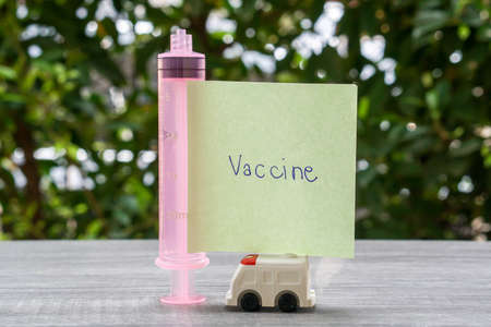 human health for   prevention concern concept -vaccine word on stick note with ambulance van Stock Photo