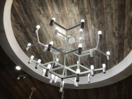 hanging white glow chandelier on the ceiling of dining room Stock Photo