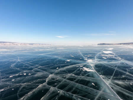 cracks on the thick frozen Baikal lake in winter season with sunny blue sky