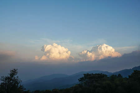 nature landscape of mountain top view with big white fluffy clouds in sunny blue sky
