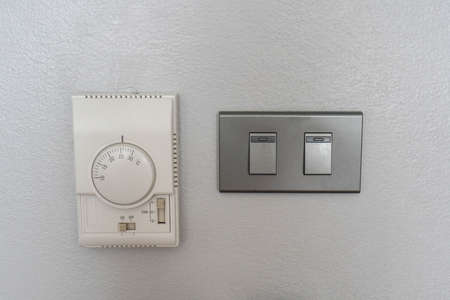 air conditioning setting panel with light switch on the house wall